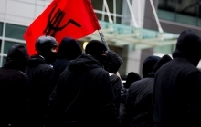 Antifa members carrying red flag