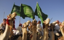 Saudis riding camels wave the country's national flag