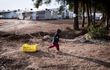 A child drags a crate at a refugee camp for Syrians and Kurds north of Athens. Children under age 14 make up nearly half of the