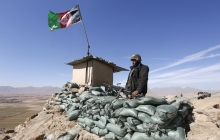 A soldier stands guard in the desert next to an Afghan flag