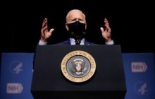 President Joe Biden wears a black mask and gestures with both hands as he speaks from a podium with the presidential seal