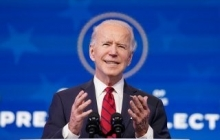 Biden speaks and gestures with his hands. A circle from the background frames Biden's head, almost like a halo.