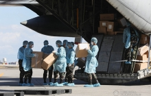 People in hair coverings, masks, gowns, gloves, and booties unload aid packages from China