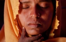 A tear comes through the closed eyes and down the cheek of Roshid Jan, a Rohingya refugee, and her son's hand touches her chin