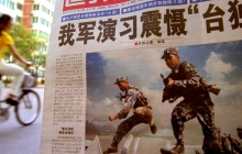 A cyclist rides behind a newspaper with a front-page photo of the People's Liberation Army soldiers doing a military exercise