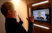A person faces a screen showing a person making the same gesture and facial expression