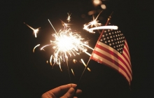 A small American flag is held in front of a sparkler