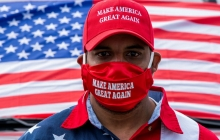 A man in a red Make America Great Again hat, matching mask, and flag-themed shirt stands in front of a US flag