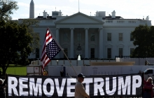 """An upside-down US flag hangs in front of the White House, over a large banner saying """"REMOVE TRUMP"""""""