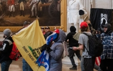 Insurrectionists wth flags and signs inside the Capitol building