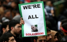 """A man in a crowd holds up a sign saying """"WE'RE ALL SOLEIMANI"""""""