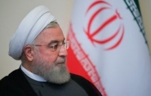 A 2019 picture of Iranian President Hassan Rouhani, seated in three-quarter profile in front of an Iranian flag