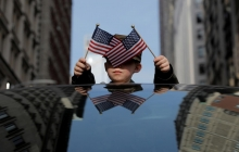 A kid sticks out of the sunroof of a car, holding a small US flag in each hand
