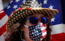 A person wears an American flag face mask, as well as a similarly-themed cowboy hat; an American flag flied in the background