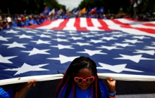 Many people, all wearing blue shirts, hold the borders of a giant American flag