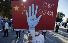 """Someone holds a """"Stop China"""" sign at an October 1 protest in the Uighur community in Istanbul"""