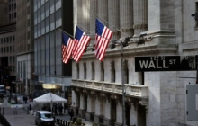 A street sign for Wall Street appears in front of three US flags hanging out of a columned building
