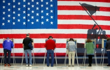 People stand at voting booths, with an American flag image taking up the whole wall behind them, and a shadow of a flag-raising