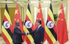 Chinese President Xi shakes hands with Ugandan President Museveni before a meeting in Beijing