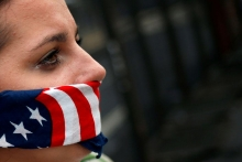 Crying women with American flag bandanna over mouth