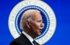 Biden in profile, with a blue background, including a blurred Presidential Seal
