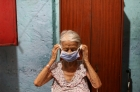 An elderly woman puts on a face mask