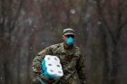 A man in military fatigues and a face mask carries a package of toilet paper as snow falls