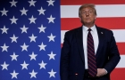 Trump stands in front of a large American flag