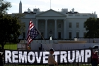 "An upside-down US flag hangs in front of the White House, over a large banner saying ""REMOVE TRUMP"""