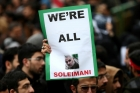 "A man in a crowd holds up a sign saying ""WE'RE ALL SOLEIMANI"""