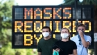 "Three people wearing masks walk in front of a large electronic road sign saying, ""MASKS REQUIRED BY [LAW]"""