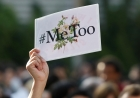 A person holds up a sign saying #MeToo over a picture of flowers