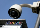Against a clear blue sky, a surveillance camera looms overhead and a Google building rises in the background