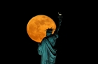 Behind a mask-covered Statue of Liberty, an orange moon glows against a dark sky