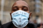 """A Black person wears a surgical mask that says """"RACISM IS A PANDEMIC"""""""