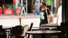 A woman wearing a mask walks by empty tables at a restaurant