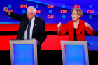 Senator Bernie Sanders and Senator Elizabeth Warren stand at their podiums during a CNN debate