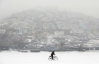 A man rides a bicycle in the snow in Kabul