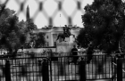 The White House, seen through a chain-link fence, with multiple rows of additional fencing in front of it