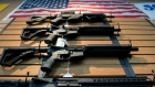 A picture, taken from below, of a wall with guns on it and an American flag at the top