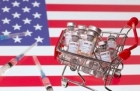 An image of a United States flag, with a cart full of vials of covid-19 vaccines and scattered needles superimposed on top