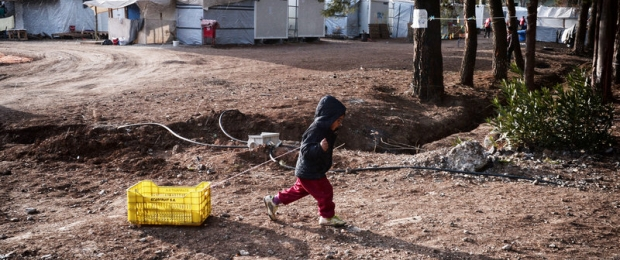 A child drags a crate at a refugee camp for Syrians and Kurds north of Athen